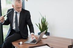 摆在他的有高尔夫俱乐部的办公室的一个年长可敬的人 他坐在膝上型计算机后的桌面 图库摄影