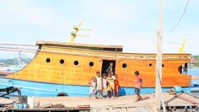 摆在传统papuan前面的孩子和十几岁运送 库存图片