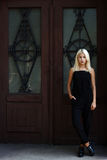 摆在伯根地门背景的美丽的年轻白肤金发的女孩  黑色礼服的性感的妇女 背景的女孩 免版税库存图片
