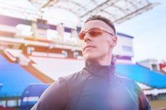 摆在体育场的连续轨道的英俊的运动人 免版税库存照片