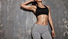 摆在体育衣裳的美丽的妇女 与完善的身体形状的肉欲的健身模型 健康生活方式,饮食 免版税图库摄影