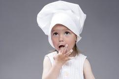 摆在作为厨师的滑稽的可爱的逗人喜爱的白种人女孩 反对灰色背景 与手指的品尝食物 免版税库存照片