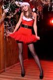 摆在作为性感的圣诞老人帮手的可爱的白肤金发的女孩 免版税库存照片