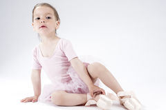 摆在作为脚趾的芭蕾舞女演员的好奇和逗人喜爱的小女孩 空白背景 免版税图库摄影