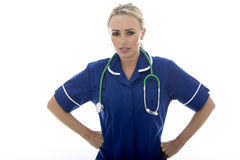 摆在作为医生或护士的可爱的年轻严厉的不快乐的妇女 免版税库存照片