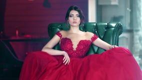 摆在使用与惊人的晚礼服中景的确信的时兴的年轻性感的妇女 影视素材