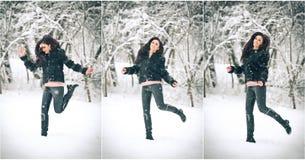 摆在使用在冬天风景的黑色的可爱的深色的女孩 有长的头发的美丽的少妇享用雪的 免版税图库摄影
