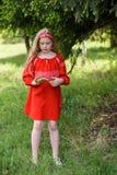 摆在俄国传统红色礼服的逗人喜爱的白肤金发的少女在杉树附近 库存图片
