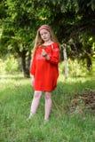 摆在俄国传统红色礼服的逗人喜爱的白肤金发的少女在杉树附近 免版税库存图片