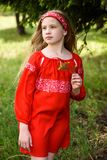摆在俄国传统红色礼服的逗人喜爱的白肤金发的少女在杉树附近 库存照片