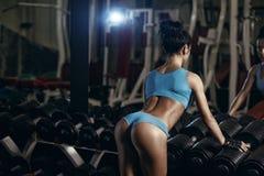 摆在健身房的后面观点的深色的性感的健身女孩 免版税库存图片