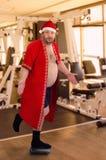 摆在健身房的左腿的肥胖圣诞老人 免版税库存照片