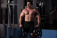 摆在健身房的美丽,强有力,大力士 免版税库存照片