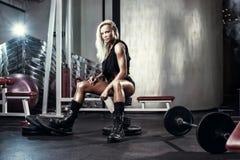 摆在健身房的长凳的健身白肤金发的性感的妇女 免版税库存照片