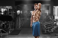 摆在健身房,形状胃肠的性感的肌肉人 强的男性赤裸躯干吸收,解决 库存图片