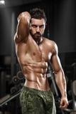 摆在健身房,形状胃肠的性感的肌肉人 强的男性赤裸躯干吸收,解决 库存照片