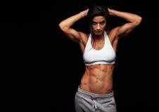 摆在健身衣物的肌肉妇女 免版税图库摄影