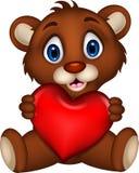 摆在充满心脏爱的逗人喜爱的婴孩棕熊动画片 免版税库存照片