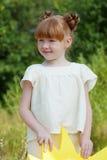 摆在公园的可爱的红发女孩的图象 免版税库存图片