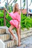 摆在公园的桃红色礼服的白肤金发的妇女 免版税图库摄影