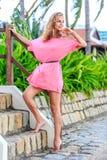 摆在公园的桃红色礼服的白肤金发的妇女 库存照片