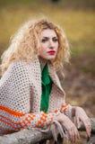 摆在公园的美丽的妇女在秋天季节期间。佩带绿色女衬衫和大披肩摆在的白肤金发的女孩室外。长的公平的头发 免版税库存照片