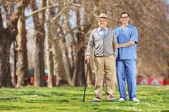 摆在公园的老人和一位男性护士 图库摄影