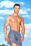 摆在公园的肌肉人在夏天 免版税库存图片