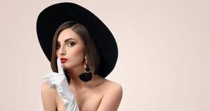 摆在典雅的时髦的女人戴一个帽子在演播室 库存照片