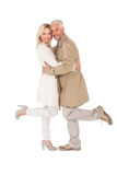 摆在军用防水短大衣的愉快的夫妇 免版税库存照片