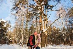 摆在冬天森林里的爱恋的夫妇 免版税库存图片