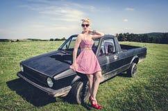 摆在减速火箭的汽车旁边的性感的画报女孩 免版税库存照片