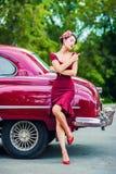 摆在减速火箭的汽车旁边的紫色礼服的美丽的女孩 免版税库存图片