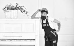摆在减速火箭的钢琴旁边的英俊的有胡子的搬家工人隔绝在白色背景 从讨厌的工作的小断裂 库存图片