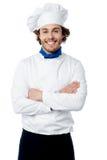 摆在制服的确信的年轻人厨师 免版税库存照片