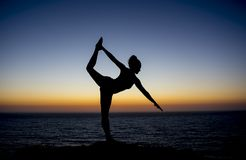 摆在剪影的日落的瑜伽老师研了 库存照片