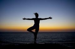 摆在剪影的日落的瑜伽老师研了 免版税库存照片