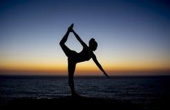 摆在剪影的日落的瑜伽老师研了 库存图片