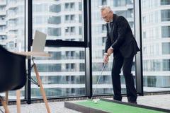 摆在办公室的一套严密的西装的一个年长可敬的人打一场微型高尔夫球赛 免版税库存图片