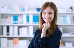 摆在办公室的美丽的妇女 免版税库存图片