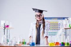 摆在化学实验室的微笑的小科学家 库存图片