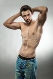 摆在半赤裸的英俊的肌肉人 免版税库存照片