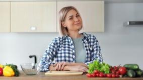 摆在厨房的微笑的偶然年轻女人由新鲜蔬菜中等特写镜头围拢了 影视素材