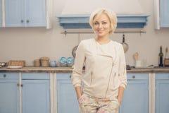 摆在厨房里的白肤金发的夫人 库存照片