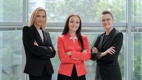 摆在反对一个轻的办公室的背景的西装的三名年轻可爱的妇女 头和下级 股票录像