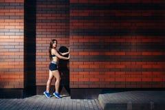 摆在反对与copyspace的砖墙背景的运动服的一个可爱的少妇 户外培训 库存照片