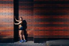 摆在反对与copyspace的砖墙背景的运动服的一个可爱的少妇 户外培训 图库摄影