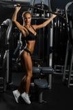 摆在反对健身房,充分的身体形象的内衣的性感,肌肉少妇 免版税库存照片