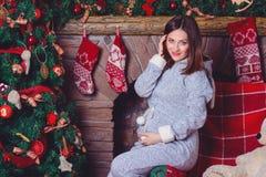 摆在反对壁炉和圣诞树的孕妇特写镜头照片 免版税库存照片