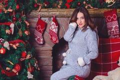 摆在反对壁炉和圣诞树的孕妇特写镜头照片 图库摄影